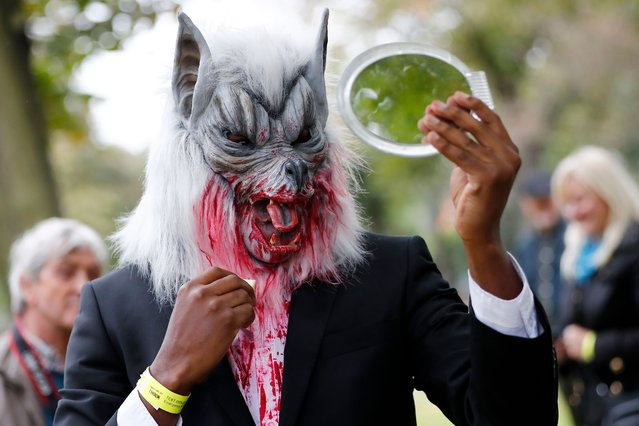 """A participant checks theuir costume before taking part in a in a """"Zombie Walk"""" on World Zombie Day, in London on October 7, 2017. (Photo by Tolga Akmen/AFP Photo)"""
