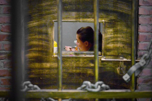 This picture taken on September 9, 2014 shows a woman having her dinner at a prison themed restaurant in Tianjin. (Photo by Wang Zhao/AFP Photo)