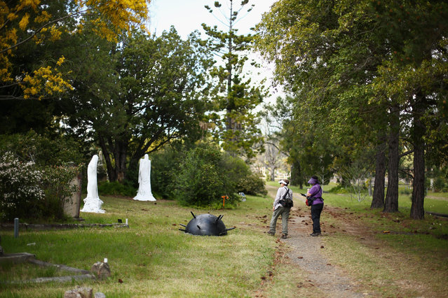 "Visitors walk towards ""Two Figures and a Sea Mine"" by Stephen Harrison at Rookwood Cemetery on September 15, 2014 in Sydney, Australia. (Photo by Mark Kolbe/Getty Images)"