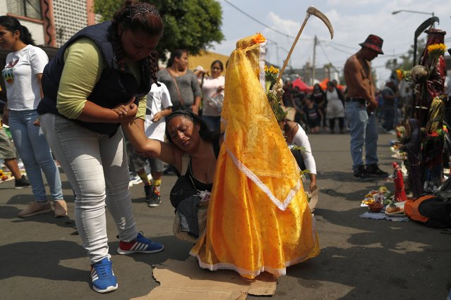 "A friend helps as Victoria Moreno, 43, struggles to arrive on her knees to the altar of the ""Santa Muerte"", or Death Saint, a pledge Moreno had made when asking the saint to help save her daughter who was suffering from appendicitis, in Mexico City's Tepito neighborhood, Monday, June 1, 2020. Despite the ongoing coronavirus pandemic, thousands of devotees, few wearing face masks amidst the dense crowd, made the monthly pilgrimage Monday to pray or give thanks to Santa Muerte, one of several unofficial folk saints worshipped in Mexico. (Photo by Rebecca Blackwell/AP Photo)"