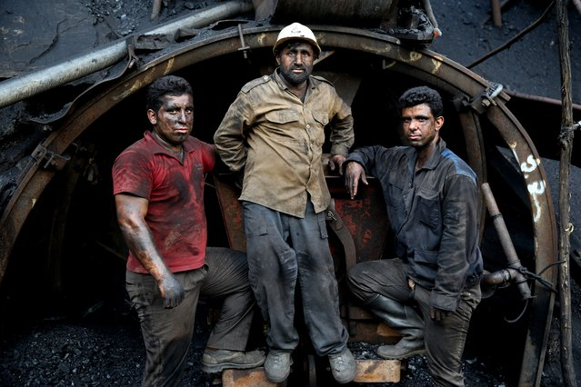 In this Monday, Aug. 18, 2014 photo, Iranian coal miners pose for a photograph at a mine on a mountain in Mazandaran province, near the city of Zirab 212 kilometers (132 miles) northeast of the capital Tehran, Iran. (Photo by Ebrahim Noroozi/AP Photo)