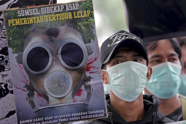 Protesters hold a rally outside the governor of South Sumatra's office calling for the immediate end to the forest fires in the province in Palembang, South Sumatra province, September 15, 2015 in this photo taken by Antara Foto. A worsening haze across northern Indonesia, neighbouring Singapore and parts of Malaysia on Tuesday forced some schools to close and airlines to cancel flights, while Indonesia ordered a crackdown against lighting fires to clear forested land. (Photo by Nova Wahyudi/Reuters/Antara Foto)