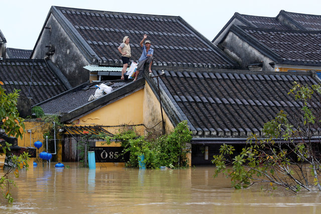 People stand on the roof of their house along submerged street in the UNESCO heritage ancient town of Hoi An after typhoon Damrey hits Vietnam on November 5, 2017. (Photo by Reuters/Kham)