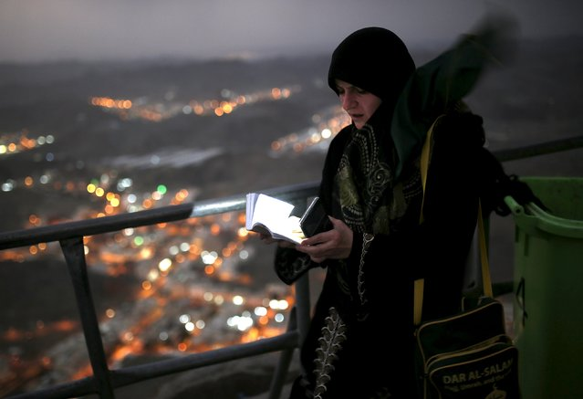 A Muslim pilgrim uses her mobile phone to light up as she reads from the Quran after visiting Hera cave, where Muslims believe Prophet Mohammad received the first words of the Koran through Gabriel, at the top of Mount Al-Noor during the annual haj pilgrimage in the holy city of Mecca, September 21, 2015. (Photo by Ahmad Masood/Reuters)