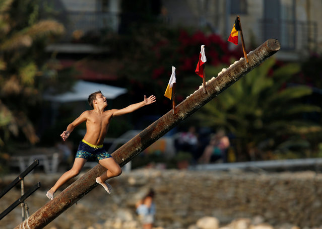 """A child tries to grab a flag on the """"gostra"""", a pole covered in grease, during the religious feast of St Julian, patron of the town of St Julian's, outside Valletta, Malta, August 27, 2016. In the traditional """"gostra"""", a game stretching back to the Middle Ages, young men, women and children have to make their way to the top and try to uproot one of the flags to win prizes. From May to September in Malta, there is hardly any weekend when a town or a village is not celebrating the feast of its patron saint or other saints revered in different churches. (Photo by Darrin Zammit Lupi/Reuters)"""