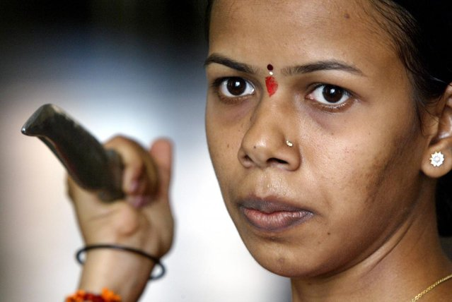Sujata Jadeja, a primary school teacher and an activist of the Vishwa Hindu Parishad or World Hindu Council, takes part in weapons training during a summer camp in Bombay May 17, 2003. (Photo by Sherwin Crasto/Reuters)