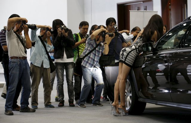 Visitors take pictures of a promotional model posing next to an Audi car during the Imported Auto Expo in Beijing, China, September 24, 2015. (Photo by Kim Kyung-Hoon/Reuters)