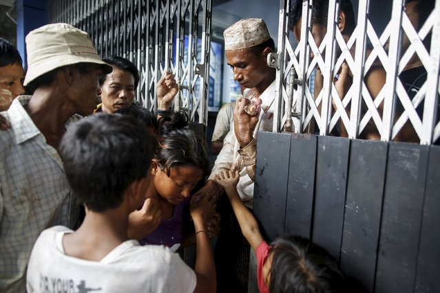 People line up in front of a donor's home to receive meat during Eid al-Adha in Yangon, Myanmar, September 25, 2015. (Photo by Soe Zeya Tun/Reuters)