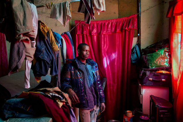 """Edward, a 20-year-old carpenter from Malawi, in the small room he shares with four other migrants in one of the derelict """"hijacked"""" buildings. He makes $24 per week, which is just enough for his living and transport expenses. (Photo by Jonathan Torgovnik/Getty Images)"""