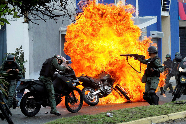 """Riot security forces clash with demonstrators as a motorcycle is set on fire during a protest against Venezuelan President Nicolas Maduro's government in San Cristobal, Venezuela, May 29, 2017. Carlos Eduardo Ramirez: """"Security forces arrived to disperse demonstrators that already had burned two taxis and a bus, throwing tear gas and pellets and the demonstrators' response was to throw molotov cocktails and one of those petrol bombs reached a National Guard member, setting him and the motorbike on fire"""". (Photo by Carlos Garcia Rawlins/Reuters)"""