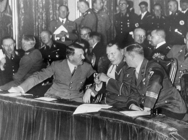 """When Chancellor Adolf Hitler called a private meeting of German Nazis for January 3, 1935 and excluded even Nazi newspapermen, rumors were rife that an upheaval in the Nazi party was under way. Hitler denied the rumors, however, saying the meeting was an """"unofficial New Year's party"""". This exclusive photograph, taken inside the Berlin State Opera House, shows the opera party that followed the meeting. Chancellor Hitler (second from left) talks to Premier Goering and storm trooper Chief of Staff Victor Lutze. Others high in the Nazi party are in the opera box, listening to a performance of Wagner's """"Tannhauser"""". (Photo by AP Photo)"""