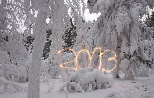A reveller writes the number 2013 with sparklers ahead of New Year's Day at an air temperature of about -25 degrees Celsius (-13 F) in a forest outside Russia's Siberian city of Krasnoyarsk December 31, 2012. Picture taken with long exposure on December 31, 2012. (Photo by Ilya Naymushin/Reuters)