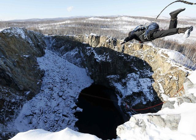 "A member of the ""Exit Point"" amateur rope-jumping group takes a rope jump from a 120-metre (394 feet) high rock down to a man-made crater called ""Tuimsky Proval"" (Tuimsky cavity), with the air temperature at about minus 15 degrees Celsius (5 degrees Fahrenheit), outside the town of Tuim in Khakassia region, October 18, 2014. (Photo by Ilya Naymushin/Reuters)"