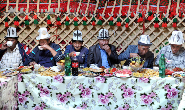 Men enjoy a feast at the 2016 World Nomad Games in Cholpon-Ata, Kyrgyzstan on September 5, 2016. (Photo by Viktor Drachev/TASS via Getty Images)