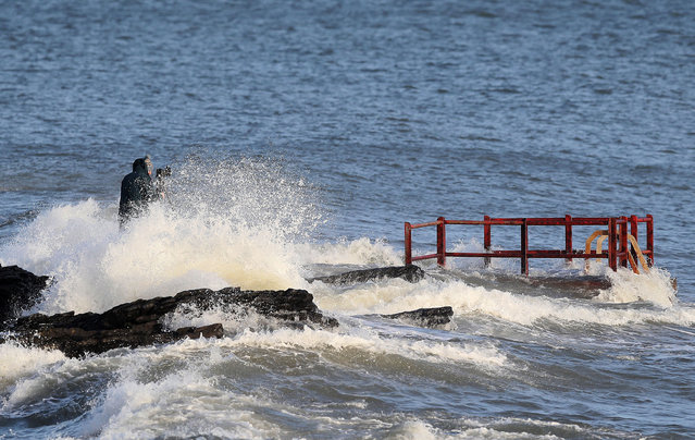 A man taking photographs gets caught by crashing waves at High Rock, Portmarnock, Ireland on January 2, 2018. Storm Eleanor, the fifth named storm of the season will bring a very windy spell to the UK and Ireland on Tuesday night and Wednesday. (Photo by Brian Lawless/PA Wire)