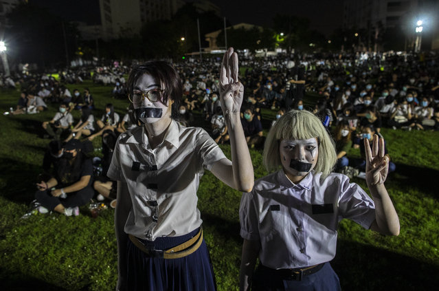 Pro-democracy students with tape covering their mouths raise a three-finger salute, a symbol of resistance, during a protest rally at Mahidol University in Nakhan Pathom, Thailand, Tuesday, August 18, 2020. Student protesters have stepped up pressure on the government with three core demands: holding new elections, amending the constitution and ending the intimidation of critics of the government. (Photo by Gemunu Amarasinghe/AP Photo)