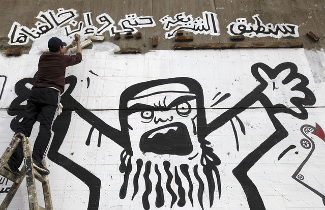 A man works on graffiti representing the Muslim Brotherhood along Mohamed Mahmoud street near Tahrir Square in Cairo, on January 24, 2013. (Photo by Amr Abdallah Dalsh/Reuters/The Atlantic)