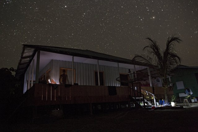 A man stands on the deck of his house at Vila Nova do Amana community in the Sustainable Development Reserve, in Amazonas state,  Brazil, September 24, 2015. (Photo by Bruno Kelly/Reuters)