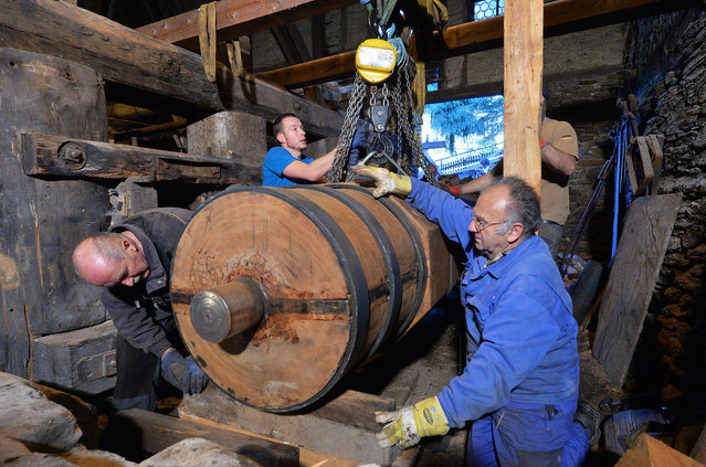 "Using a crane, employees of the company ""Muehlenbau Schumann"" insert a new shaft into the ""Frohnau hammer"" in Annaberg-Buchholz, Germany, November 3, 2014. The shaft measures over 9 meters and was produced from a 270-year-old oak trunk weighing over ten tons. The motor element is the most important part of a hammer works, dating back to the 17th century. (Photo by Hendrik Schmidt/EPA)"