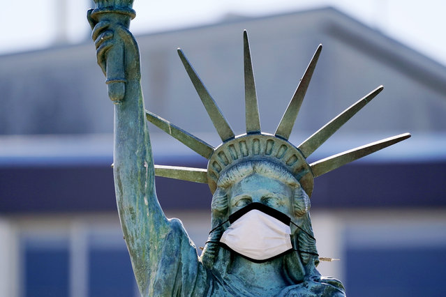 The face on a replica of the Statue of Liberty covers with a protective face mask against the coronavirus Wednesday, August 26, 2020, in Seattle. The 1/18th scale replica on Seattle's Alki Beach was erected in 1952 and recast in 2006. (Photo by Elaine Thompson/AP Photo)