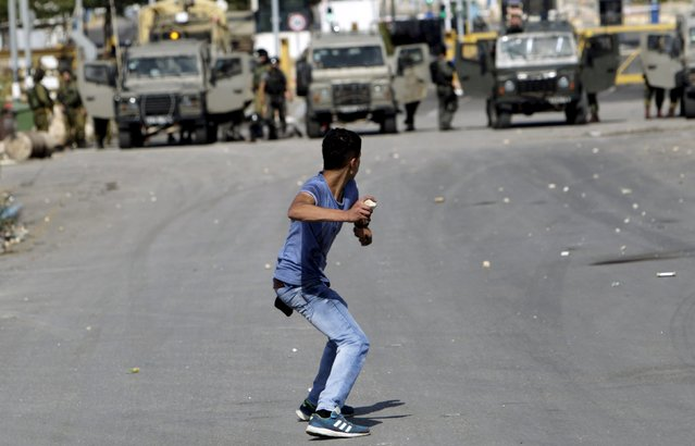 A Palestinian protester hurls stones at Israeli troops during clashes in the West Bank city of Jenin October 9, 2015. (Photo by Mohammed Ballas/Reuters)