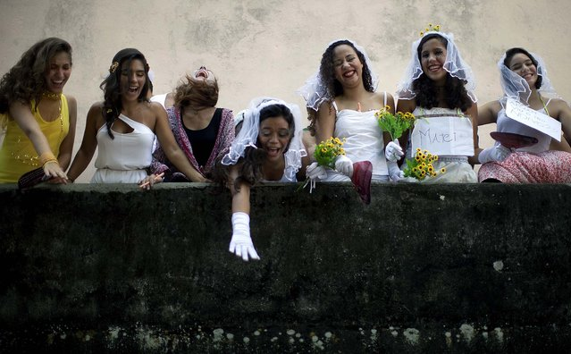 """Revelers participate in the """"Carmelitas"""" street parade in Rio. """"Carmelitas"""" is a band started in 1990 by a group of friends who gathered for soccer and drinks just outside a Carmelite convent. Jokes about the possibility of nuns escaping to join the party gave rise to the band, which parades twice: once at the beginning of Carnival and then on the last day. (Photo by Felipe Dana/Associated Press)"""