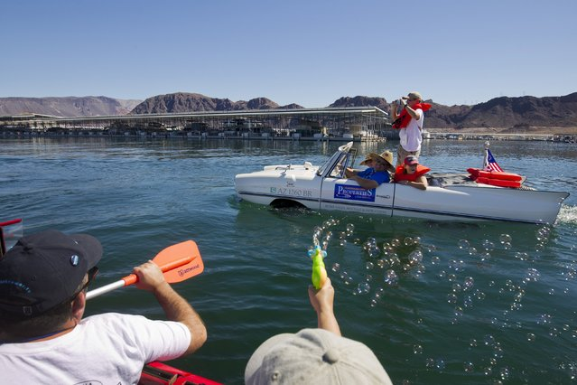 A 1965 Amphicar driven by Dean Baker of Lake Havasu, Arizona heads out for a trip to Hoover Dam during the first Las Vegas Amphicar Swim-in at Lake Mead near Las Vegas, Nevada October 9, 2015. The German-made Amphicar was produced from 1961-1968. (Photo by Steve Marcus/Reuters)