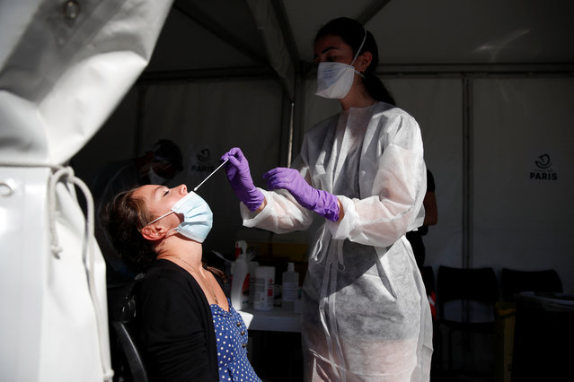 A health worker, wearing a protective suit and a face mask, prepares to administer a nasal swab to a patient at a testing site for the coronavirus disease (COVID-19) in Paris, France, September 14, 2020. France sees a substantial increase of Covid-19 cases. (Photo by Gonzalo Fuentes/Reuters)