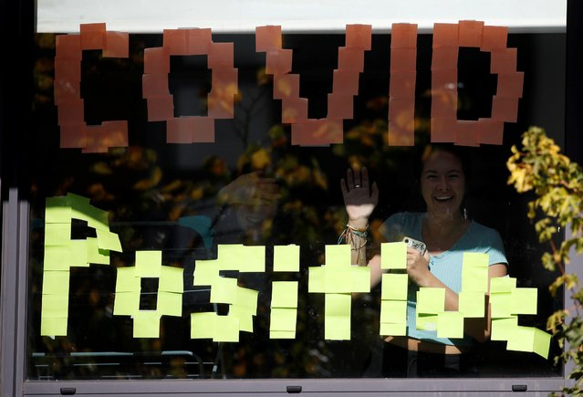 """People wave through the window of a student accommodation building with a """"Covid Positive"""" sign displayed in it, following the outbreak of the coronavirus disease (COVID-19 in Manchester, Britain, September 27, 2020. (Photo by Phil Noble/Reuters)"""