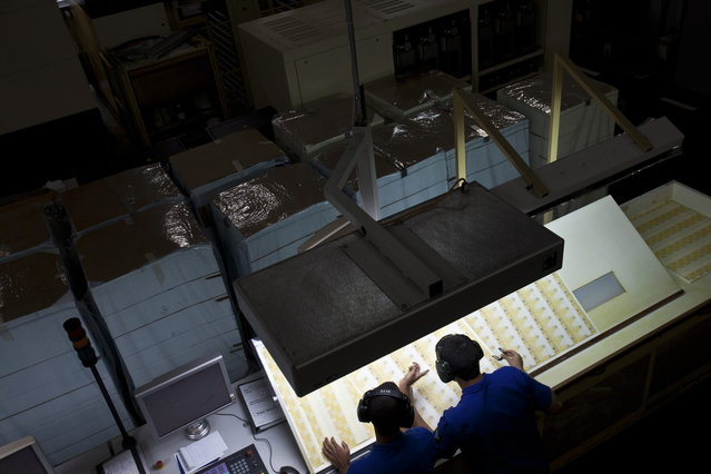 Workers inspect prints of R$ 20 Brazilian reais bills during the production process at the Casa da Moeda, the national mint, in the Santa Cruz suburb of Rio de Janeiro, Brazil, on Tuesday, March 5, 2013. Brazil is likely to keep its key interest rate at a record low for the third straight meeting, as policy makers are caught between a fragile economic recovery and faster-than-expected inflation. (Photo by Dado Galdieri/Bloomberg)