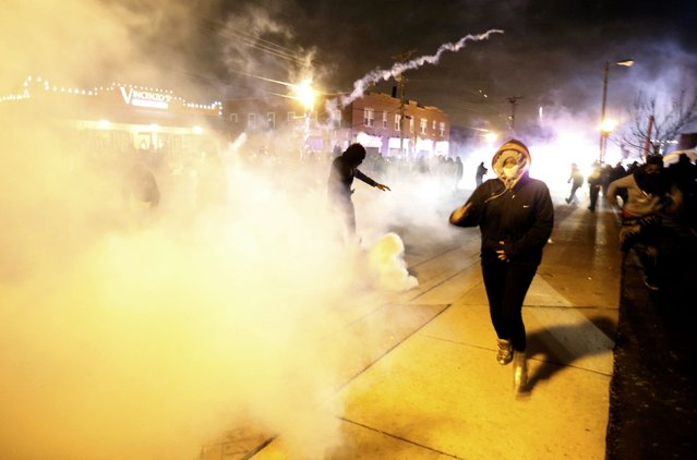 Protesters run from a cloud of tear gas after a grand jury returned no indictment in the shooting of Michael Brown in Ferguson, Missouri, November 24, 2014. (Photo by Jim Young/Reuters)