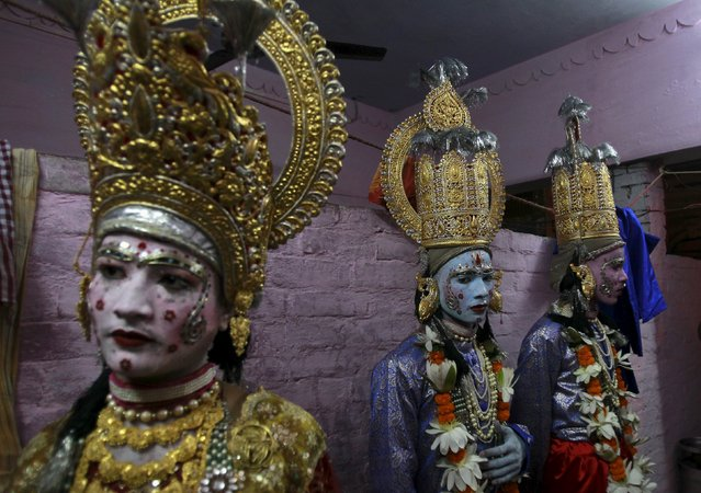 """Artists stand as they wait to take part in a religious procession ahead of the Hindu festival of Dussehra in Allahabad, India, October 15, 2015. Effigies of the 10-headed demon king """"Ravana"""" are burnt on Dussehra, the Hindu festival that commemorates the triumph of Lord Rama over the Ravana, marking the victory of good over evil. Dussehra falls on October 22. (Photo by Jitendra Prakash/Reuters)"""