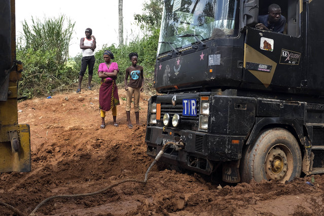 Semi-trucks delivering supplies to Gueckedou, Guinea Conakry, Saturday November 22, 2014, are stuck in heavy mud on the road from Macenta. Neighboring Mali on Saturday confirmed a new case of Ebola and said two more suspected patients are being tested, raising concern about a further spread of the disease which has already killed at least five people in the country. (Photo by Jerome Delay/AP Photo)