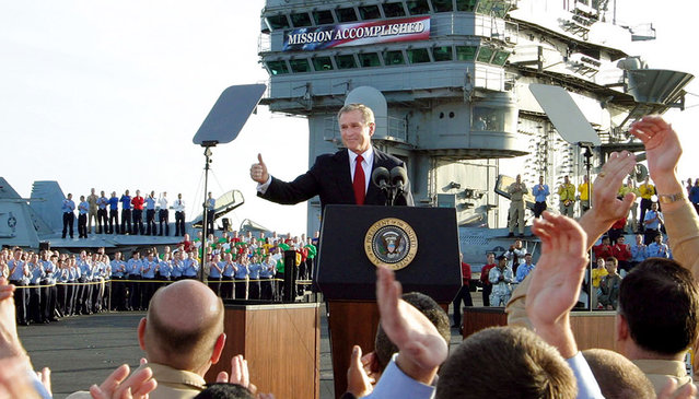 President Bush gives a thumbs-up sign after declaring the end of major combat in Iraq as he speaks aboard the aircraft carrier USS Abraham Lincoln off the California coast, on May 1, 2003. (Photo by J. Scott Applewhite/AP Photo/The Atlantic)