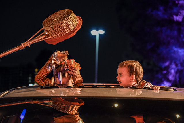 A Haunt O'ween staff pours candy treats to a child using a basket with a long wooden handle to maintain social distancing at Haunt O'ween in Woodland Hills, Calif., on October 15, 2020. (Photo by Kevin Lendio for NBC News)