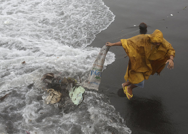 A Filipino resident dumps debris which he retrieved from his house as strong waves from Typhoon Hagupit battered a coastal village in Legazpi, Albay province, eastern Philippines Monday, December 8, 2014. (Photo by Aaron Favila/AP Photo)