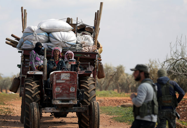Internally displaced people ride with their belongings in the town of Inab, eastern Afrin, Syria March 14, 2018. (Photo by Khalil Ashawi/Reuters)