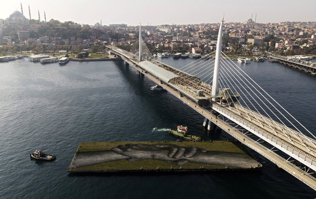"""An aerial view shows an artwork by French-Swiss street artist Saype called """"Beyond Walls"""" on a floating barge over the Golden Horn in Istanbul, Turkey October 23, 2020. The art pieces created by Saype in Istanbul are the eighth step of a project to create a spray-painted """"human chain"""" across the world to encourage humanity and equality. (Photo by Murad Sezer/Reuters)"""
