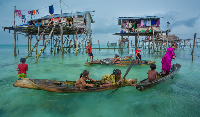 "Bajau seaborne settlement in Semporna, Sabah, Malaysia. ""Sometimes called sea gypsies, the Bajau have little allegiance to any country. They distrust Malaysia, the Philippines and Indonesia. They live in boats and small stilted homes. They are fishermen and speak their own language"". (Photo by Art Wolfe/The Guardian)"
