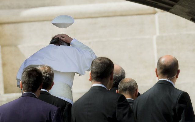 A gust of wind blows the Pope's Francis hat, on April 10, 2013. (Photo by Alessandra Tarantino/AP Photo)