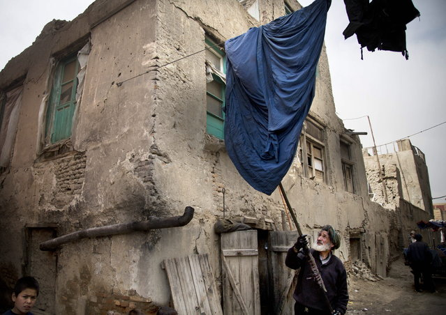 Haji Hussain, 75, who colors clothing for 40 years, takes a freshly colored burqa out for drying outside his small shop in the old town of Kabul, Afghanistan, Monday, April 15, 2013. (Photo by Anja Niedringhaus/AP Photo)
