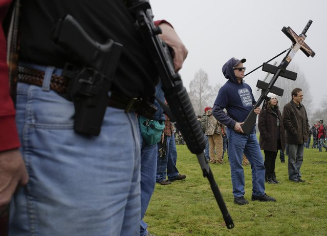 People carry their firearms as gun rights advocates rally against Initiative 594 at the state capitol in Olympia, Washington December 13, 2014. (Photo by Jason Redmond/Reuters)