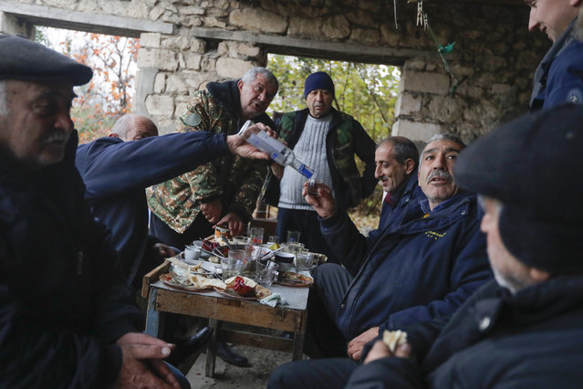 Ethnic Armenians drink vodka during their last dinner before leaving their homes in the village of Maraga, in the Martakert area, in the separatist region of Nagorno-Karabakh, Wednesday, November 18, 2020. (Photo by Sergei Grits/AP Photo)