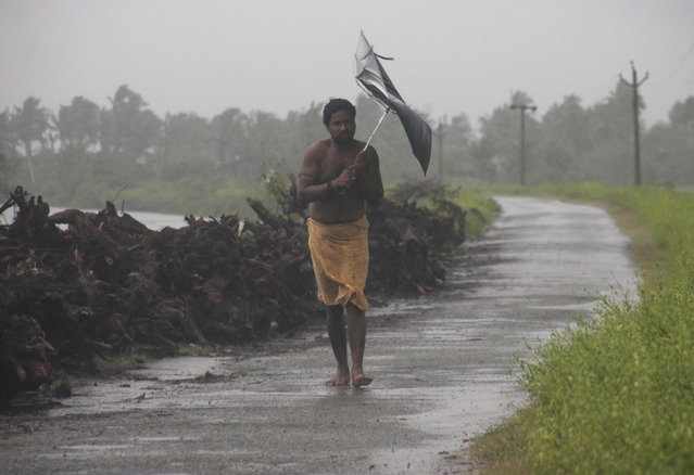 A man struggles with an umbrella in strong winds and rain caused by Cyclone Hudhud in Gopalpur in Ganjam district in the eastern Indian state of Odisha October 12, 2014. (Photo by Reuters/Stringer)