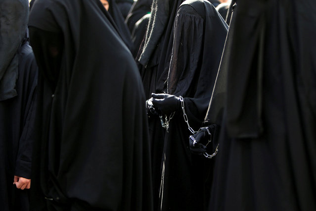 Muslim Shi'ite women are chained to each other march during a re-enactment of the battle of Kerbala during a mourning process, one day before the Shi'ites will mark the day of Ashura, in Nabatiyeh, Lebanon October 11, 2016. (Photo by Ali Hashisho/Reuters)