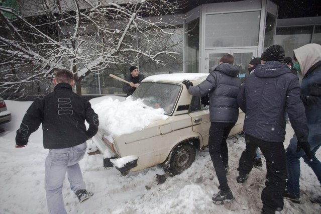 In this photo taken on Friday, March 15, 2013, members of a pro-Kremlin youth group attack pushers of spice, a synthetic drug, one of which is swinging a bat at them in Moscow, Russia. Russian officials and anti-drugs campaigners say that spice has become one of the most dangerous drugs widely available to youngsters and almost impossible to ban because of the constantly changing chemical ingredients. (Photo by Alexander Zemlianichenko Jr/AP Photo)