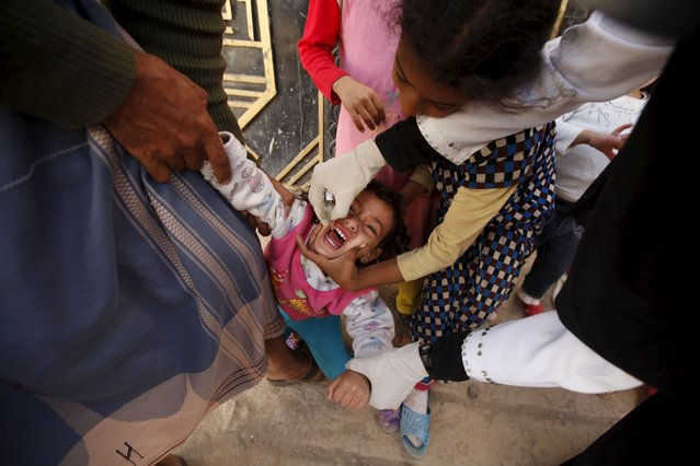 A girl receives polio vaccination outside her house in Yemen's capital Sanaa November 9, 2015. According to local media, Yemen started on Monday a three-day house-to-house polio vaccination campaign that aims to target around five million children under five years of age. (Photo by Khaled Abdullah/Reuters)