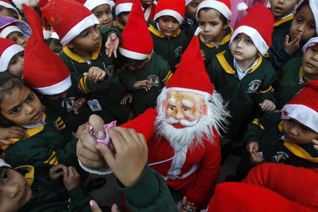 A student in a Santa Claus costume distributes sweets amongst school children during Christmas celebrations in the northern Indian city of Chandigarh December 24, 2014. (Photo by Ajay Verma/Reuters)
