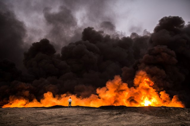 A man stands in front of a fire from oil that has been set ablaze in the Qayyarah area, some 60 kilometres (35 miles) south of Mosul, on October 19, 2016, during an operation by Iraqi forces against Islamic State (IS) group jihadists to retake the main hub city. (Photo by Yasin Akgul/AFP Photo)