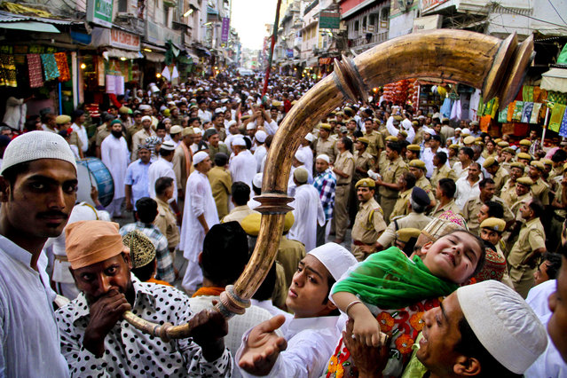 A pilgrim plays a horn during the flag hoisting ceremony to begin the Urs and Sufi festival  in Ajmer, India, on May 7, 2013. The event attracts thousands of devotees to commemorate the 13th century death of their most famous saint, Moinuddin Chishti. (Photo by Deepak Sharma/Associated Press)